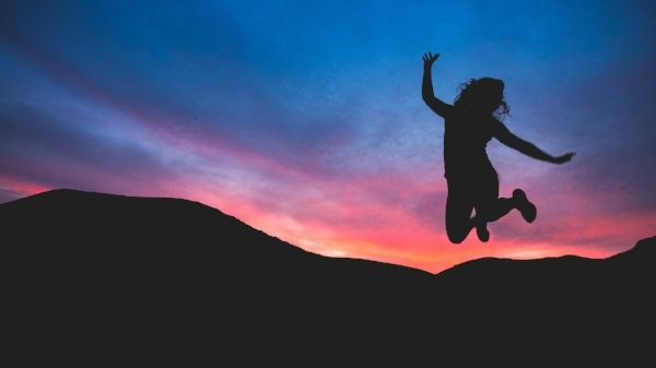 silhouette of person jumping with mountains and night sky