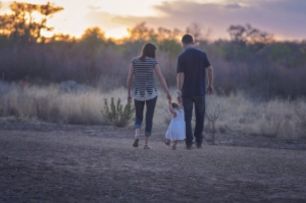 family walking down dirt path at sunset