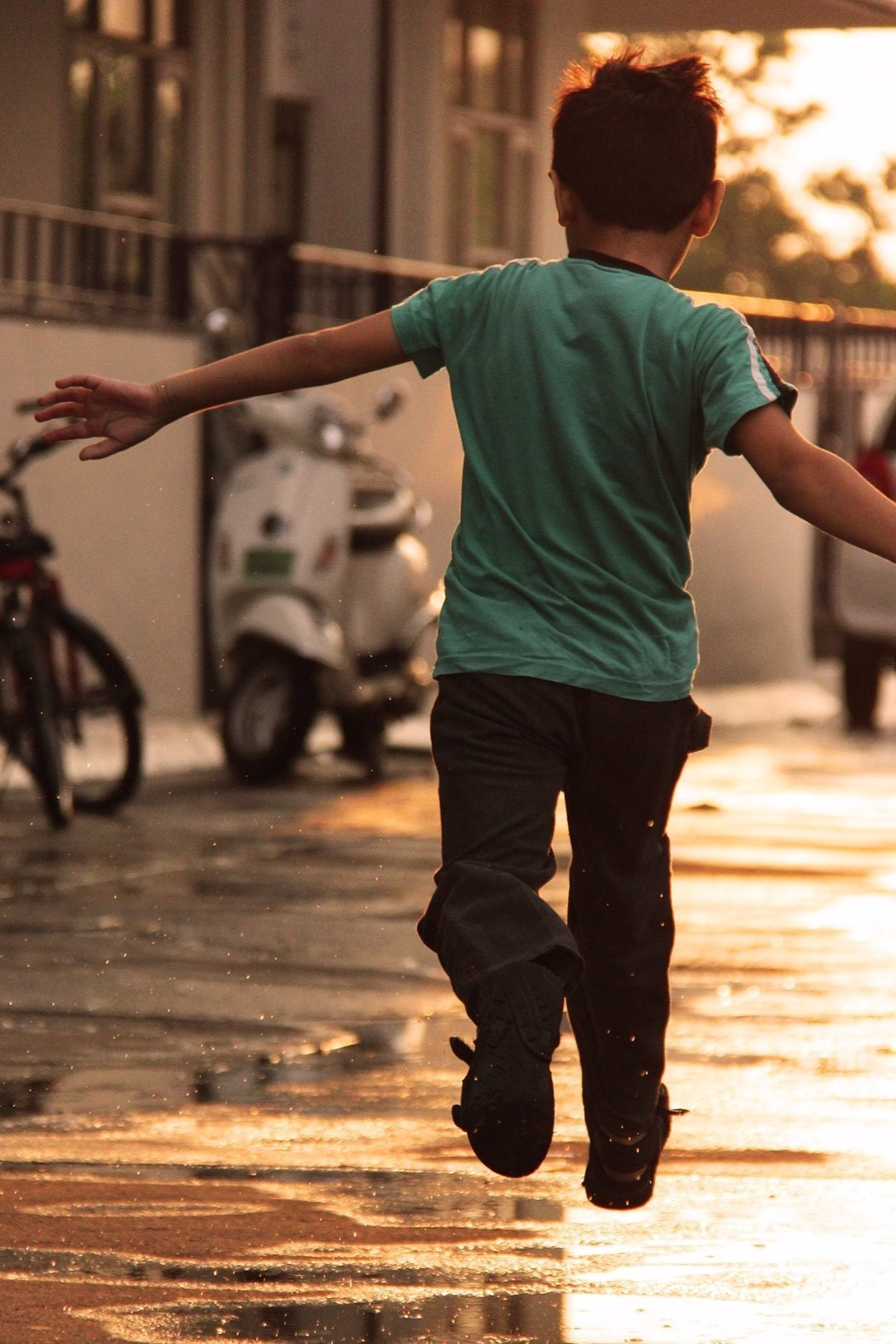 boy in green shirt running down wet street