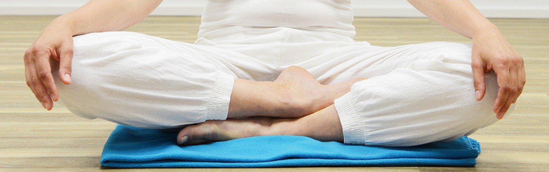 person sitting on blue mat doing meditation